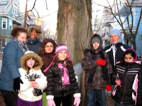 A group of students from John F. Kennedy Elementary School in Somerville stand before the sugar maple tree they've just tapped.