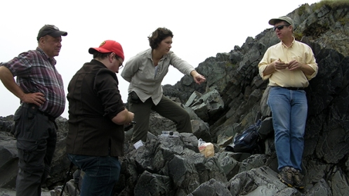 Paleontologists (left to right) Guy Narbonne, Marc Laflamme, Sarah Tweedt, and Doug Erwin consider the fossils of the Mistaken Point Ecological Reserve in Newfoundland. The rocks are filled with half-a-billion-year-old treasures.