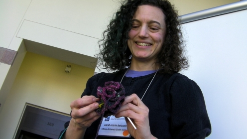 In addition to being a mathematician, sarah-marie belcastro creates fiber arts.  She shows off her crocheted hyperbolic Mobius strip.