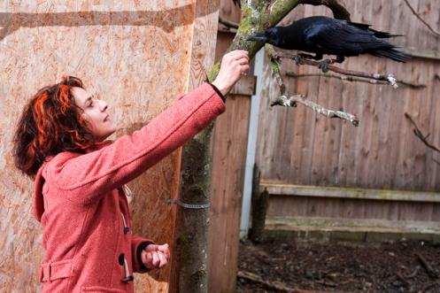 Christine Schwab offers the raven Astrid a treat.